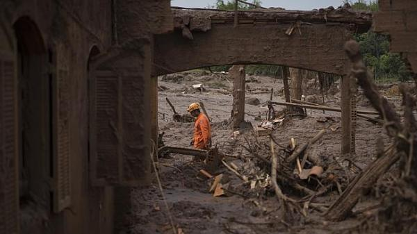 A rescue worker walks between destroyed houses after the dam disaster in Brazil.